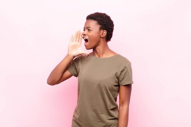 Joven mujer bonita gritando en voz alta y enojada para copiar espacio en el costado, con la mano al lado de la boca contra la pared rosa