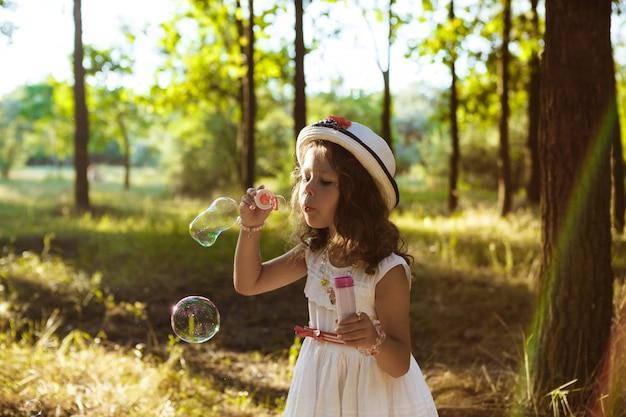 Joven mujer bonita haciendo burbujas, caminando en el parque al atardecer