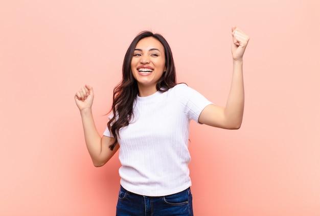 Joven mujer bonita latina gritando triunfante, luciendo emocionada, feliz y sorprendida ganadora, celebrando contra la pared plana