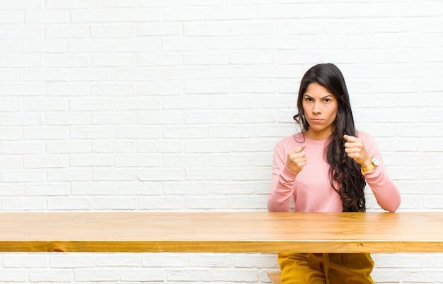 Joven mujer bonita latina que parece segura, enojada, fuerte y agresiva, con los puños listos para pelear en posición de boxeo sentado frente a una mesa
