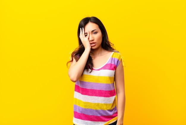 Joven mujer bonita latina que se siente aburrida, frustrada y somnolienta después de una tarea aburrida, aburrida y tediosa, sosteniendo la cara con la mano contra la pared plana