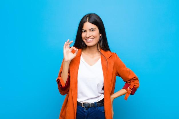 Joven mujer bonita latina se siente feliz, relajada y satisfecha, mostrando aprobación con gesto bien, sonriendo contra la pared plana