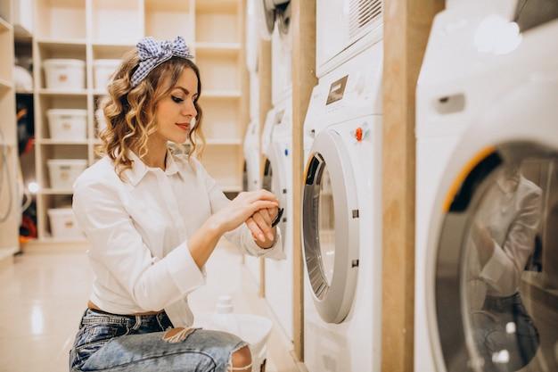 Joven mujer bonita en una lavandería