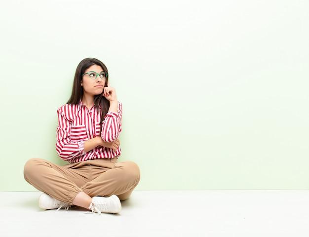 Joven mujer bonita con una mirada concentrada, preguntándose con una expresión dudosa, mirando hacia arriba y al lado sentada en el suelo