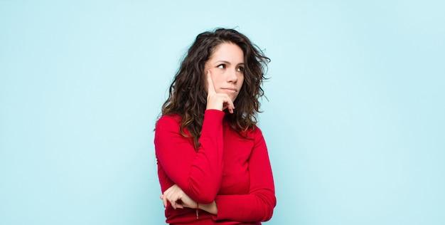 Joven mujer bonita con una mirada concentrada, preguntándose con una expresión dudosa, mirando hacia arriba y hacia un lado contra la pared azul