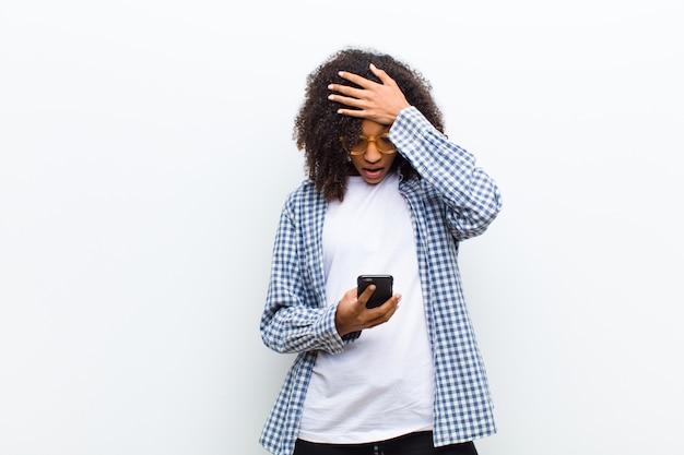 Joven mujer bonita negra con un teléfono inteligente
