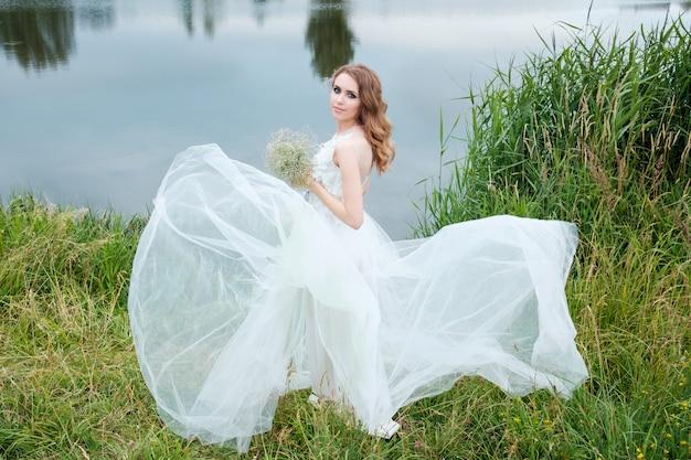 Joven mujer bonita (novia) en vestido de novia blanco al aire libre, peinado