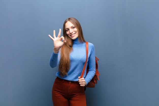 Joven mujer bonita pared azul con un espacio de copia