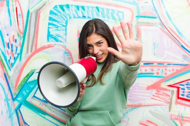 Joven mujer bonita con una pared de graffiti megáfono