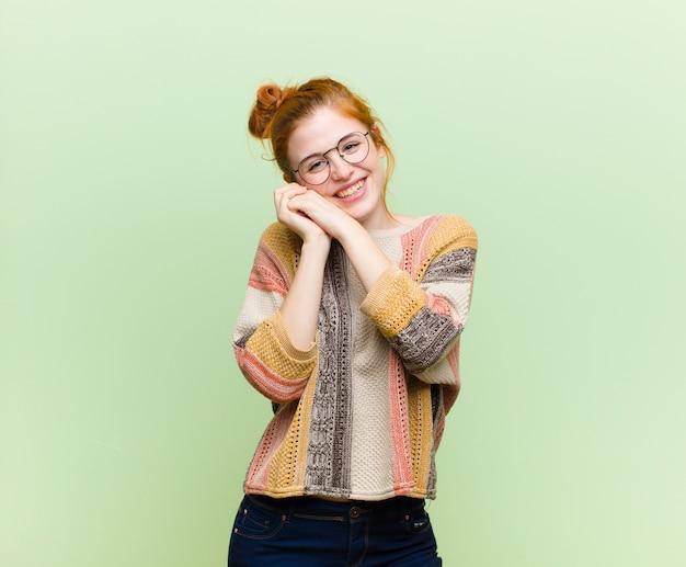 Joven mujer bonita pelirroja que se siente enamorada y se ve linda, adorable y feliz, sonriendo románticamente con las manos junto a la cara contra la pared verde