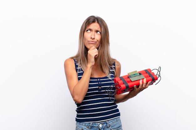 Joven mujer bonita pensando, sintiéndose dudosa y confundida, con diferentes opciones, preguntándose qué decisión tomar con una bomba de dinamita
