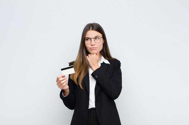 Joven mujer bonita pensando, sintiéndose dudosa y confundida, con diferentes opciones, preguntándose qué decisión tomar con una tarjeta de crédito