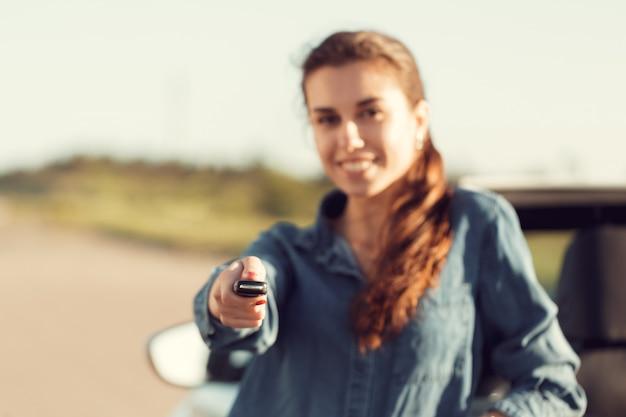 Joven mujer bonita de pie cerca de convertible con llaves en mano