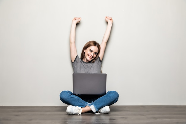 Joven mujer bonita con un portátil sentado en el suelo celebrando una victoria