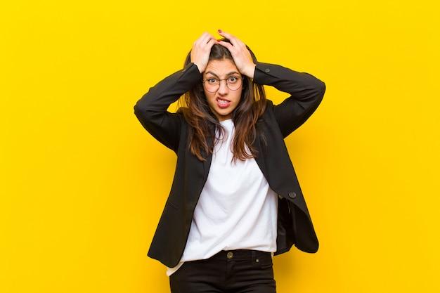 Joven mujer bonita que se siente frustrada y molesta, enferma y cansada del fracaso, harta de tareas aburridas y aburridas contra la pared naranja