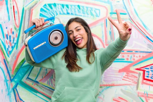 Joven mujer bonita con una radio vintage contra la pared de graffiti