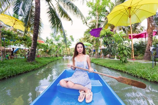 Joven mujer bonita relajante en bote de remos