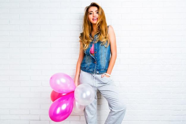 Joven mujer bonita rubia bastante elegante posando con globos de fiesta grande con chaqueta de mezclilla hipster y pantalones grises deportivos
