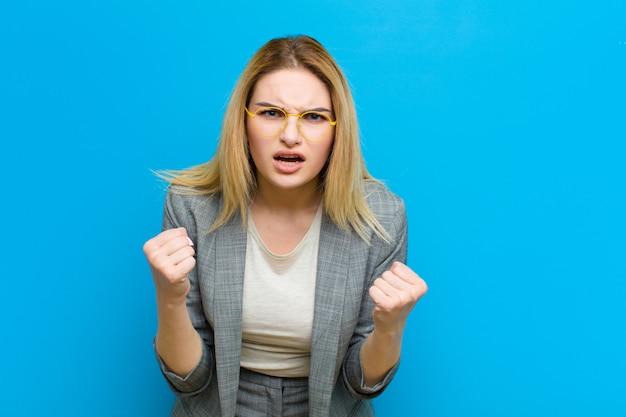 Joven mujer bonita rubia gritando agresivamente con mirada molesta, frustrada, enojada y puños apretados, furiosa contra la pared plana