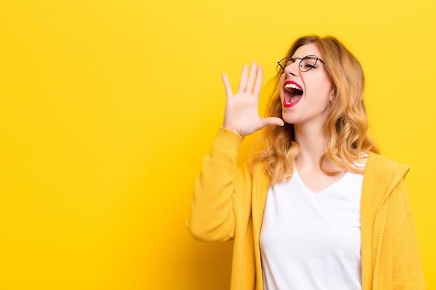 Joven mujer bonita rubia gritando en voz alta y enojada al lado, con la mano al lado de la boca sobre la pared amarilla