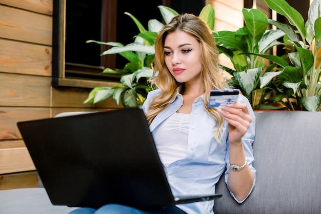 Joven mujer bonita rubia con laptop y tarjeta de crédito, sentado en el sofá en lugar de coworking moderno