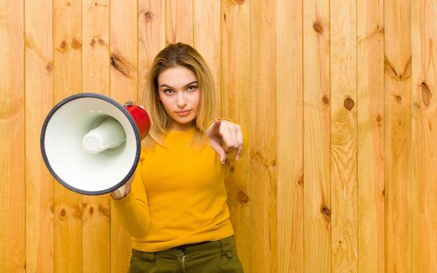 Joven mujer bonita rubia con un megáfono contra la pared de madera