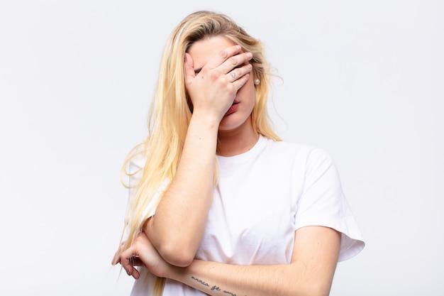 Joven mujer bonita rubia mirando estresado, avergonzado o molesto, con dolor de cabeza, cubriéndose la cara con la mano sobre la pared blanca
