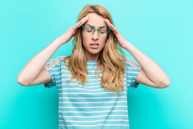 Joven mujer bonita rubia que parece estresada y frustrada, trabajando bajo presión con dolor de cabeza y con problemas sobre la pared de color
