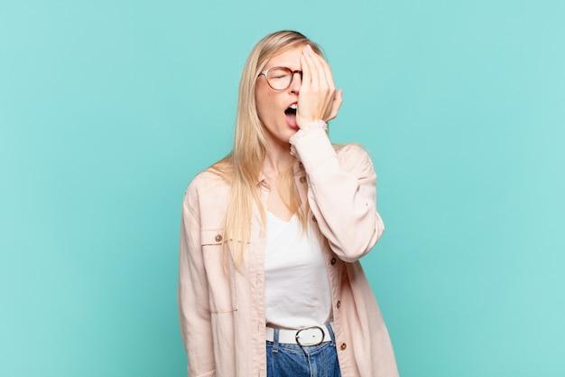 Joven mujer bonita rubia que parece somnolienta, aburrida y bostezando, con dolor de cabeza y una mano cubriendo la mitad de la cara