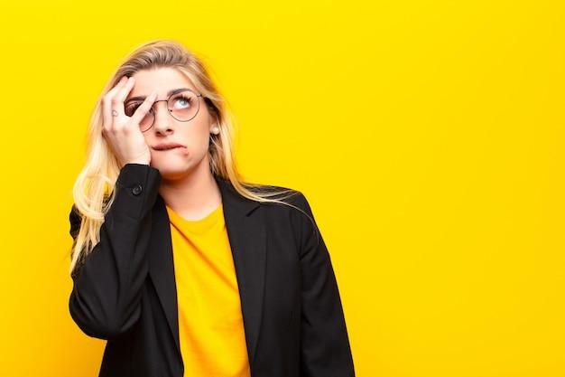 Joven mujer bonita rubia que se siente aburrida, frustrada y somnolienta después de una tarea aburrida, aburrida y tediosa, con la cara contra la pared amarilla