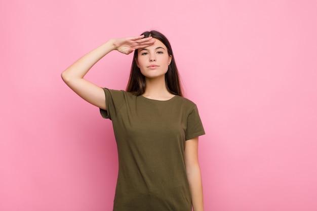 Joven mujer bonita saludando a la cámara con un saludo militar en un acto de honor y patriotismo, mostrando respeto por la pared rosa