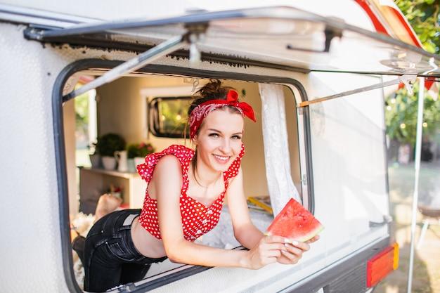 Joven mujer bonita con sandía en autocaravana