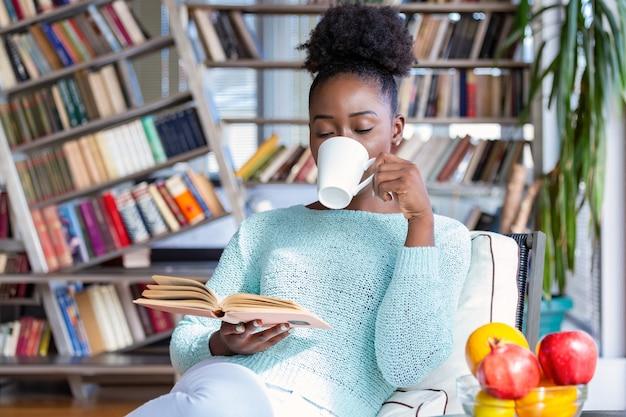 Joven mujer bonita sentada y bebiendo café mientras lee un libro