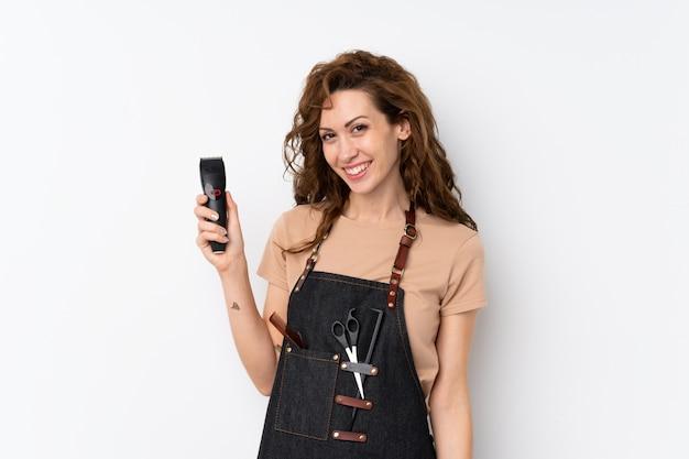 Joven mujer bonita sobre pared aislada con peluquería o vestido de barbero y sosteniendo la cortadora de cabello