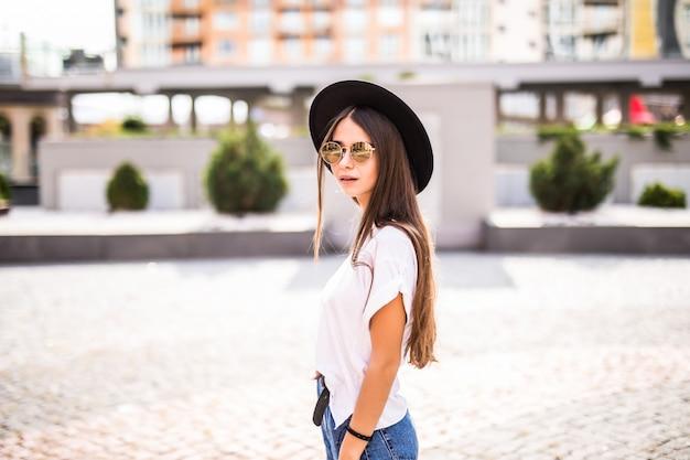 Joven mujer bonita en sombrero negro de altura completa de pie en la calle de verano