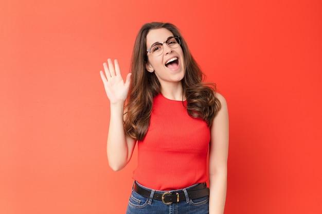 Joven mujer bonita sonriendo alegremente y alegremente, saludando con la mano, dándole la bienvenida y saludando, o diciéndole adiós contra la pared roja