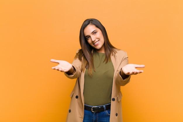 Joven mujer bonita sonriendo alegremente dando un cálido, amable, cariñoso abrazo de bienvenida, sintiéndose feliz y adorable aislado contra la pared naranja