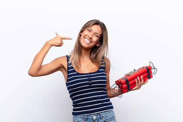 Joven mujer bonita sonriendo con confianza apuntando a su propia sonrisa amplia, actitud positiva, relajada y satisfecha con una bomba de dinamita