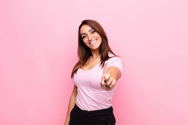 Joven mujer bonita sonriendo con orgullo y confianza haciendo la pose número uno triunfante, sintiéndose como un líder contra la pared rosa