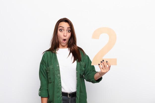 Joven mujer bonita sorprendida, sorprendida, asombrada, sosteniendo un número 2