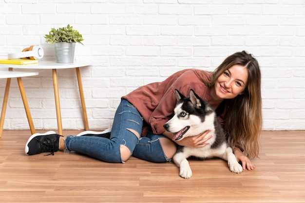 Joven mujer bonita con su perro husky sentado en el suelo en el interior