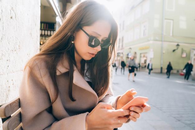 Joven mujer bonita con teléfono inteligente en la calle de la ciudad