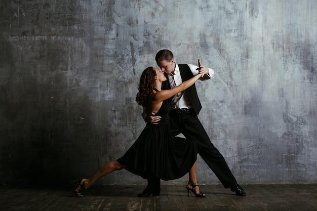 Joven mujer bonita en vestido negro y hombre baila tango