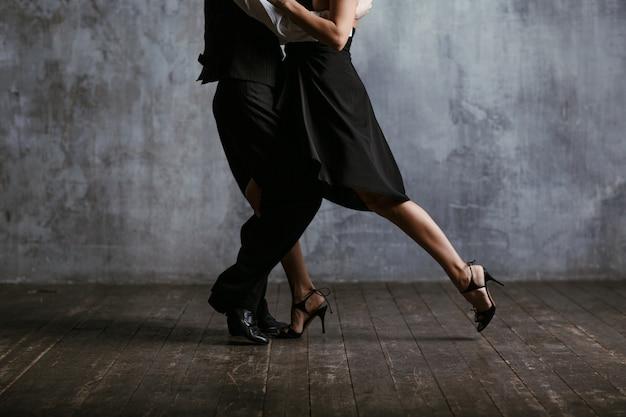 Joven mujer bonita en vestido negro y hombre bailando tango