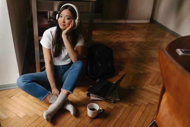 Joven mujer bronceada en jeans con estilo y calcetines blancos está mirando al frente y posando en auriculares