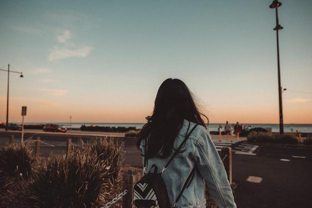 Joven mujer caminando por la acera con un cielo azul claro y espalda