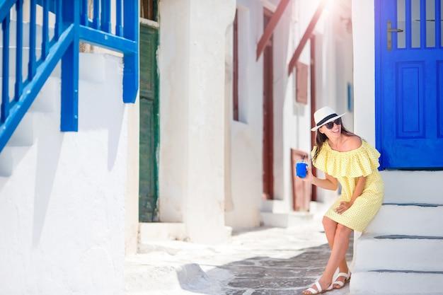 Joven mujer caminando en calles estrechas del antiguo pueblo griego en grecia