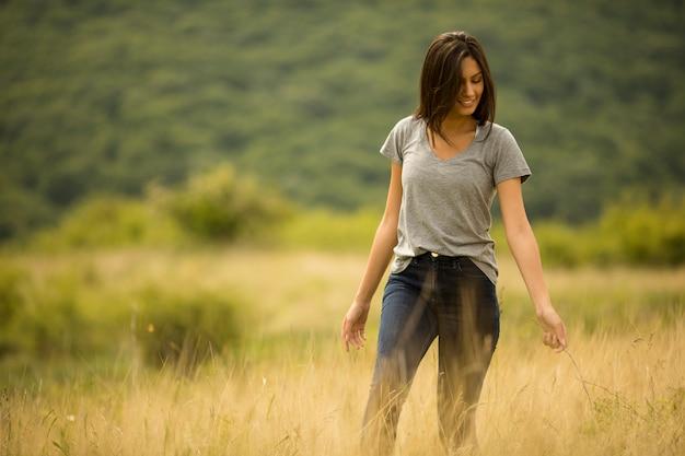 Joven mujer caminando en el campo de hierba alta