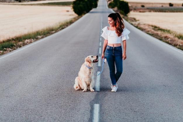 Joven mujer caminando por la carretera con su perro golden retriever al atardecer. mascotas al aire libre