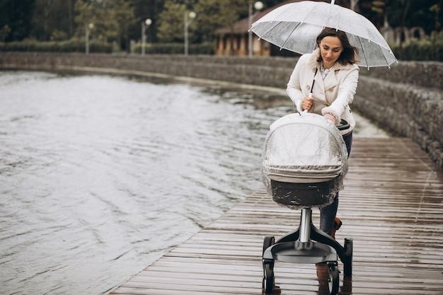 Joven mujer caminando con carro de bebé bajo el paraguas en un clima lluvioso